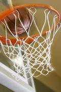 Close up of basketball entering hoop - stock photo