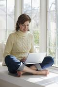Woman sitting in window alcove with laptop - stock photo