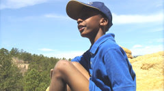 Boy on top of a mountain giving explanation. - stock footage