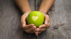 Green apple with engraved heart Stock Photos