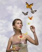 Young woman with flower and butterflies - stock photo