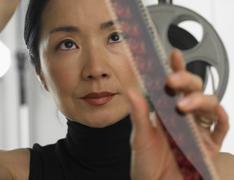 Asian woman looking at film Stock Photos