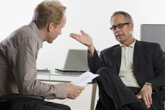 Two businessmen sitting and talking Stock Photos