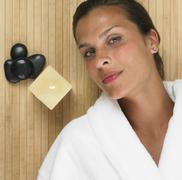Stock Photo of Woman in bathrobe laying next to stones and lit candle
