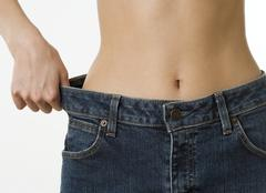 Close up of woman holding waist of pants away from hip - stock photo