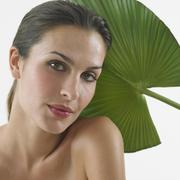 Woman with bare shoulders in front of leaf - stock photo