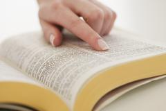 Woman's finger on page in Bible - stock photo