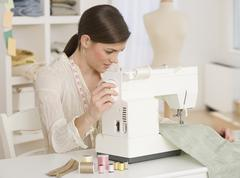 Woman using sewing machine - stock photo
