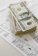 Stack of money on tax forms Stock Photos