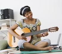 African woman playing acoustic guitar - stock photo