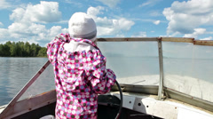 Small child standing near steering wheel in motorboat Stock Footage