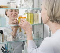 Senior woman looking in medicine cabinet - stock photo