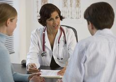 Female doctor talking to couple in office Stock Photos