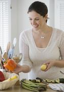 Stock Photo of Woman chopping vegetables in kitchen