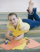 Girl cutting construction paper on floor - stock photo