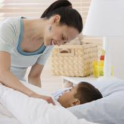 Asian mother tucking son into bed Stock Photos