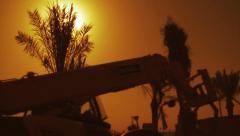 Heavy Vehicle In front Of Palmtrees in Orange Sky Stock Footage