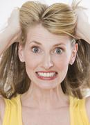 Frustrated woman pulling on hair Stock Photos
