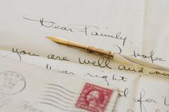 Quill pen on old letter - stock photo