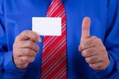 Businessman showing business card and approval sign Stock Photos