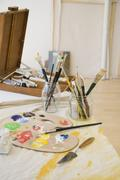 Artist?s palette and paintbrushes on table Stock Photos