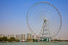 Giant ferris wheel against a high-rise city backdrop by the water Stock Photos