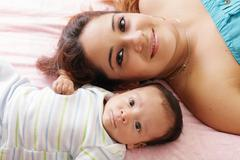 Portrait of happy young attractive hispanic mother lying with her baby on the Stock Photos