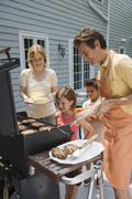 Family barbequing on deck - stock photo