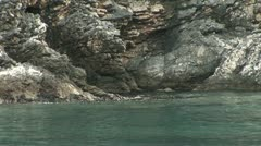 Waves evenly lapp against the rocky coastline Stock Footage