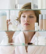 Woman looking in medicine cabinet - stock photo