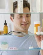 Man looking in medicine cabinet - stock photo