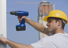 Construction worker using cordless drill - stock photo