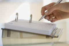 Woman writing on desk calendar - stock photo