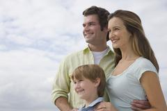 Stock Photo of Family with one child under cloudy sky