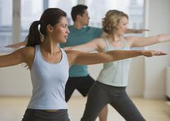 Multi-ethnic people in yoga class - stock photo