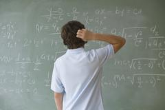 Teenaged boy looking at math equations on blackboard - stock photo
