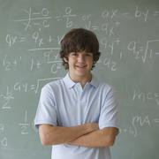 Teenaged boy in front of blackboard with math equations - stock photo