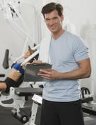 Male personal trainer writing on chart - stock photo