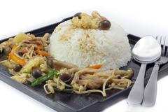 mushrooms stir fry with rice on black plate - stock photo