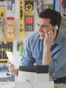 Sales clerk talking on telephone in hardware store Stock Photos