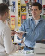 Hardware store sales clerk handing over purchase Stock Photos