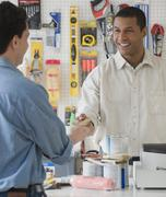 African sales clerk at hardware store handing over credit card - stock photo