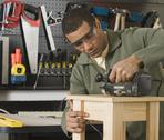 Stock Photo of African male woodworker sanding table