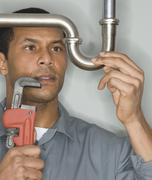 African male plumber holding wrench next to pipe Stock Photos
