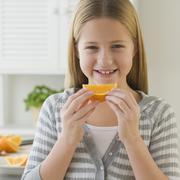 Stock Photo of Girl eating orange slice