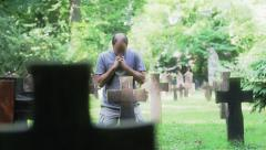 Man praying at cemetery Stock Footage