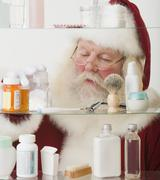 Santa Claus looking in medicine cabinet - stock photo