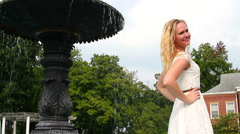 Beautiful young blonde posing near a fountain, Stock Footage