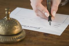 Woman filling out hotel registration Stock Photos