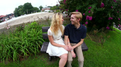 Pull away shot of young couple on bench. Stock Footage